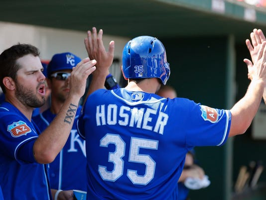 Kansas City Royals' Eric Hosmer (35) is congratulated by teammates, including Mike Moustakas, left, after Hosmer connected for a run-scoring single against the Cincinnati Reds during the first inning of a spring training baseball game, Tuesday, March 15, 2016, in Goodyear, Ariz. (AP Photo/Ross D. Franklin)