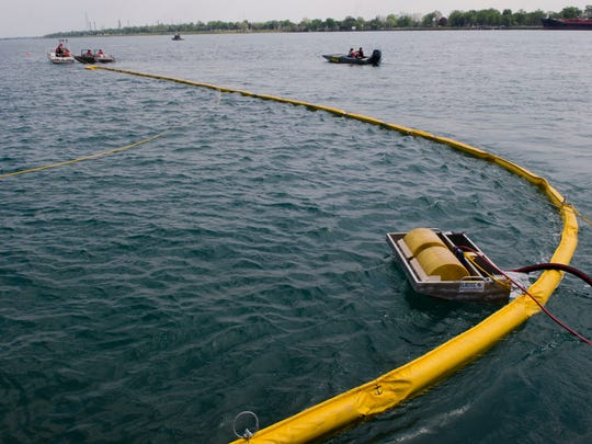 A skimmer floats in the trapped area and would suck up spilled material as small boats pull the large yellow boom during a 2016 oil spill exercise by U.S. Coast Guard and local agencies.