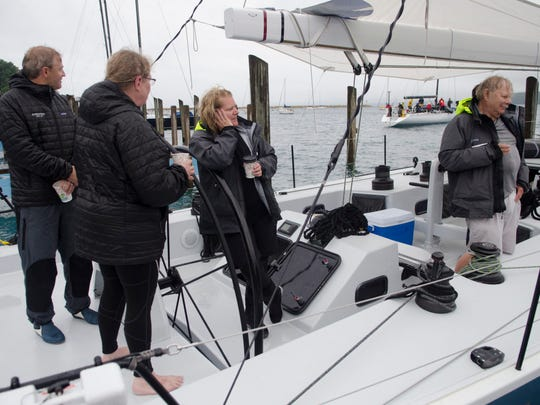 Jason Bemis, Leslie Kohler, Sarah Reichelsdorfer and Pete Reichelsdorfer, all of Sheboygan, Wisconsin relax after docking their sailboat, Evolution, Sunday, July 18 at Mackinac Island. Their boat is projected to win first place overall.