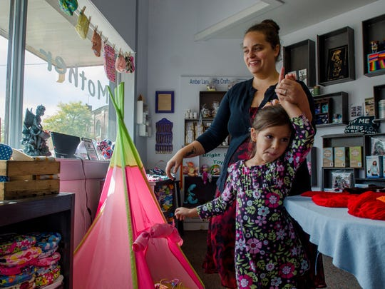 Owner Denelle Philemon walks around her store with her daughter, Eleanor, 6, Sunday, Oct. 2, 2016, at Mother Moon & Me in Sandusky.