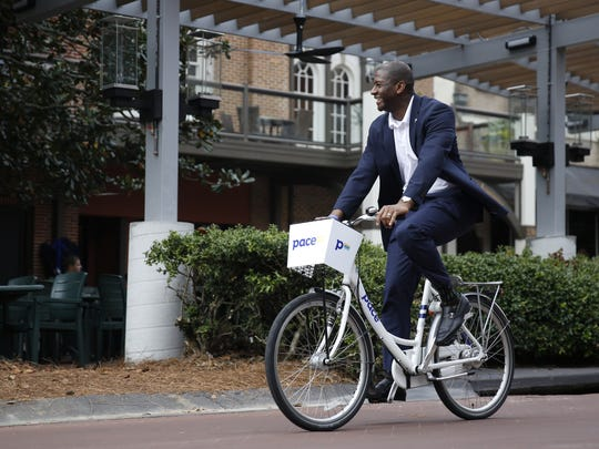 Mayor Andrew Gillum tries out a Pace bike in front