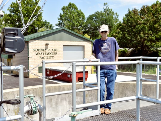 Rodney C. Abel stands on the catwalk above a wastewater tank at the treatment plant that bears his name.