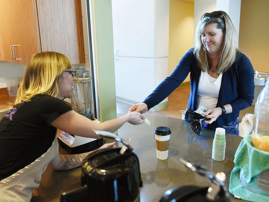 Customer Shannon Yockey pays for a cup of coffee at