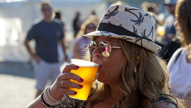 The second day of the Bacon, Bourbon and Brew Festival took place on Riverboat Row in Newport on Saturday, July 15, 2017, featuring bacon and other pork products, Kentucky bourbon and beers from local breweries. Elizabeth Crossley sips a cold draught beer from Braxton Brewing Company.