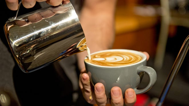 The Cincinnati Coffee Festival kicked off its weekend of coffee, tea and treats on Saturday, Nov. 11, 2017, with tastings, demonstrations, music and competitions at Cincinnati Music Hall. A contestant applies his best coffee design skills during the Latte Art Throwdown.