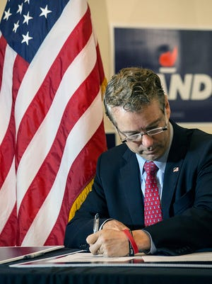 Sen. Rand Paul signs documents at the Jefferson County Republican Party West End Office on Monday, Nov. 30, 2015, declaring himself a candidate for president in Kentucky.