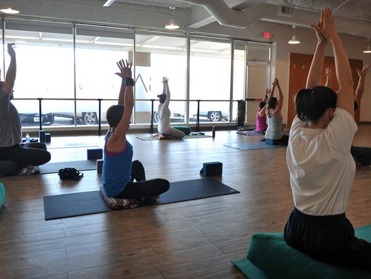 In this file photo, students in a yoga class at Balance Yoga and Barre move through a series of poses. The studio is hosting flow classes for free this Saturday at 1:30 and 3 p.m.