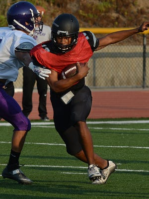 Moorpark quarterback Kado Brown scampers away from a CLU defender during a scrimmage at Moorpark College last week.