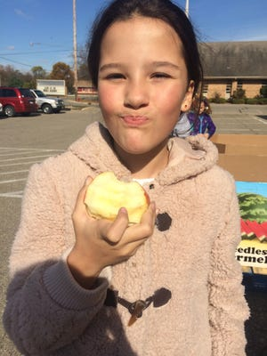 Sophia Acevedo, 10, munches on her apple Friday afternoon while she helped pack apples for Gleaners Community Food Bank as part of Michigan's Apple Crunch for National Food Day.