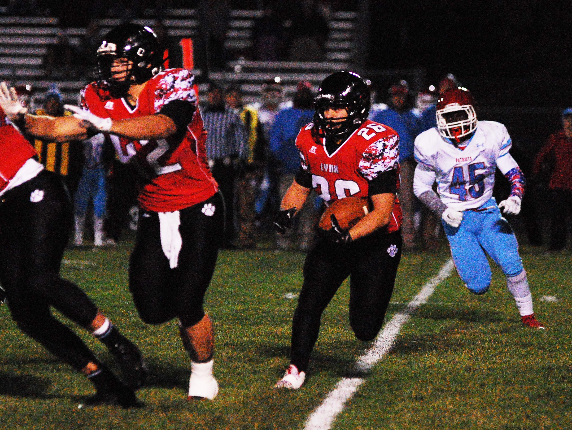 Brandon Valley's Tyler Hintz (26) gets a block from teammate Andrew Sorensen as Lincoln's Jimmy Smith is in pursuit of him. The Lynx won the 11AAA state quarterfinal game 28-14.