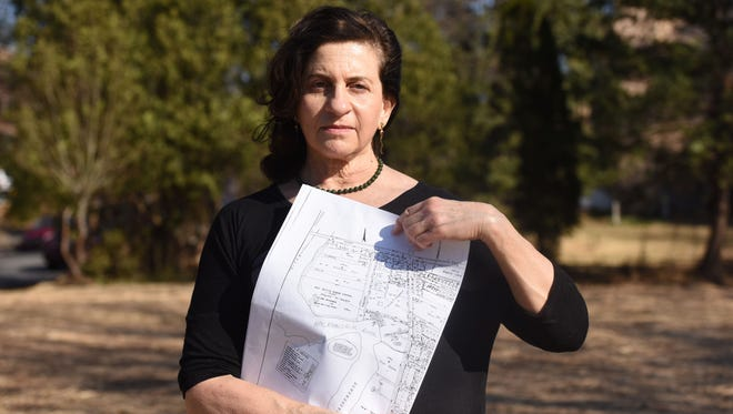 Dee Ann Ipp holds a map of the location at the burial ground that was used by native Americans and later by former slaves and was designated as historic by the township.