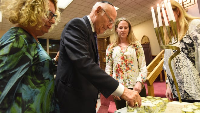Holocaust survivor Erwin Ganz lights up a candle during Holocaust Remembrance ceremony at Temple Emanuel of Pascack Valley