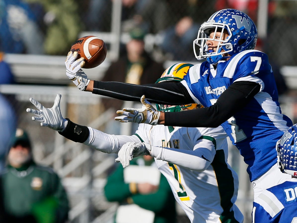 Walled Lake Western defender Cody White got his hand on the pass but Midland Dow's Mike Robb, left, made the pass reception and ran it in for a long touchdown cutting Walled Lake Western's lead to 14-7 in the first half in high school football regional final on Saturday, November 14, 2015, in Walled Lake.