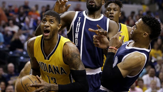 Indiana Pacers forward Paul George (13) works under the basket against Oklahoma City Thunder defenders at Bankers Life Fieldhouse on Saturday, March 19, 2016.