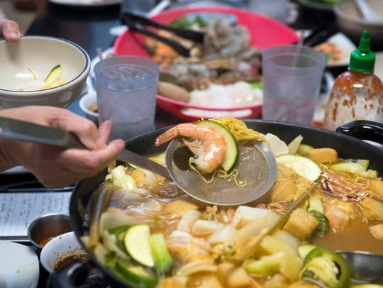 Diners enjoy a hot pot dinner at Sticky Rice Cafe on