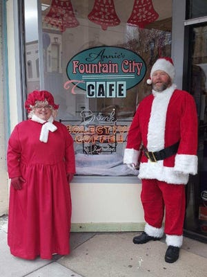 Mrs. Claus and Santa pose outside Annie's Fountain City Cafe.