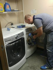 Captain Steve Wilson loads the dryer with warming shelter