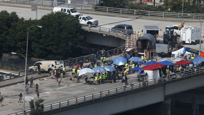 """In this Tuesday, July 8, 2014 photo, actors and extras work during the filming of 'Walking Dead,' in Atlanta. A film studio is constructing a 15-foot-high wall around a neighborhood built on the site of an old cotton gin in the small town of Senoia, Ga. The goal is to create a sort of backlot to film episodes of """"The Walking Dead"""" through November."""