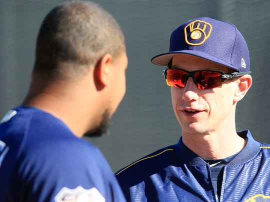 Brewers manager Craig Counsell chats with Wily Peralta in Arizona on Wednesday, the first day of spring drills for pitchers and catchers.
