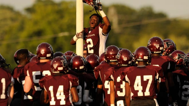 Fulton's Zach Winston (2) climbs the goal post while rallying with teammates before their season opener against Powell at Fulton High School in Knoxville on Friday, Aug. 22, 2014. Fulton won 83-3.