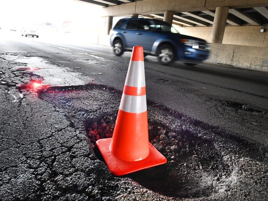 This deep pothole on the northbound Southfield Freeway, in the shadow of the Joy Road overpass, left cars with flattened tires and damaged wheels before an orange cone was placed inside it in this Tuesday, April 17, 2018 file photo.