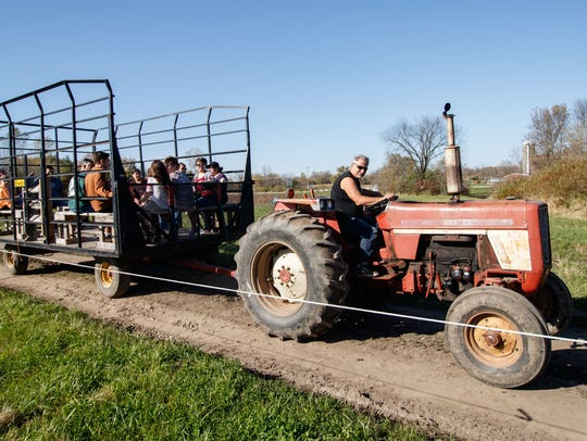 Visitors catch a wagon ride out to the pumpkin patch