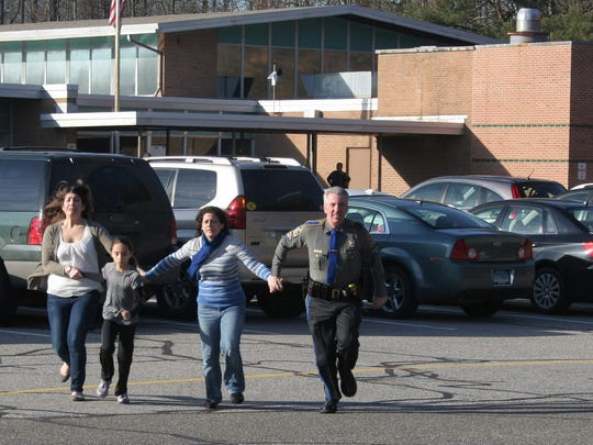 FILE - In this Friday, Dec. 14, 2012, file photo provided by the Newtown Bee, a police officer leads two women and a child from Sandy Hook Elementary School in Newtown, Conn., where a gunman opened fire, killing 26 people, including 20 children. A prosecutor is planning to release a report on the investigation into the massacre at Sandy Hook Elementary School on Monday, Nov. 25, 2013, but the public will have to wait longer for the Connecticut state police?s full accounting of the crime.(AP Photo/Newtown Bee, Shannon Hicks, File) MANDATORY CREDIT: NEWTOWN BEE, SHANNON HICKS