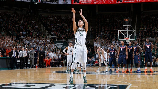 Michigan State's Bryn Forbes (5) shoots the first of two free throws on a technical foul during the final minute of an NCAA college basketball game against Illinois in East Lansing, Mich.