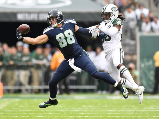 Seattle Seahawks tight end Jimmy Graham (88) makes  a one-handed, 47-yard catch despite pressure from New York Jets cornerback Marcus Williams (20).