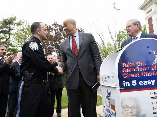 Then-Bergenfield Captain Mustafa Rabboh, left, shakes hands with U.S. Senators Cory Booker, center, as Bob Menendez, right, looks on, in Bergenfield on Friday, April 29, 2016. Rabboh will become the borough's police chief officially on August 20.