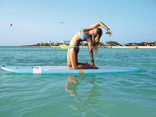 Rachel Brathen practices yoga while balancing on a paddle board at Hadicurari beach in Aruba.