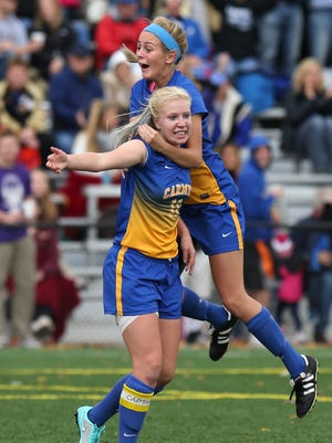 Carmel's Amanda Shaw, 11, and Emma Chambers celebrate a goal by Shaw in the first half of the game against Brebeuf during the regional championship game Saturday October 18, 2014 at Carmel. Carmel won the game.