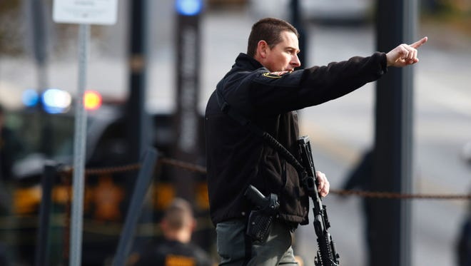 A law enforcement official motions for people to leave the area outside of a parking garage on the campus of Ohio State University as they respond to an active attack in Columbus, Ohio.