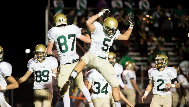York Catholic's Riley Brennan (87) and Isaiah Pineda (5) celebrate after Brennan scored a touchdown against Bermudian Springs on Friday, Oct. 20, 2017. York Catholic won 41-26.