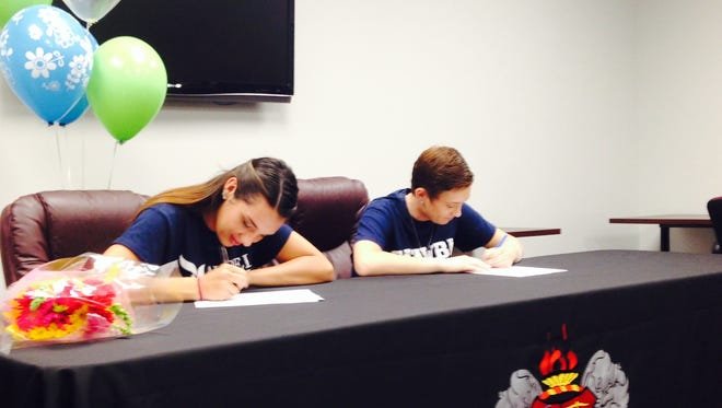 Asheville High seniors Anna Dockery, left, and Sarah Smith signed to play college sports on Thursday.