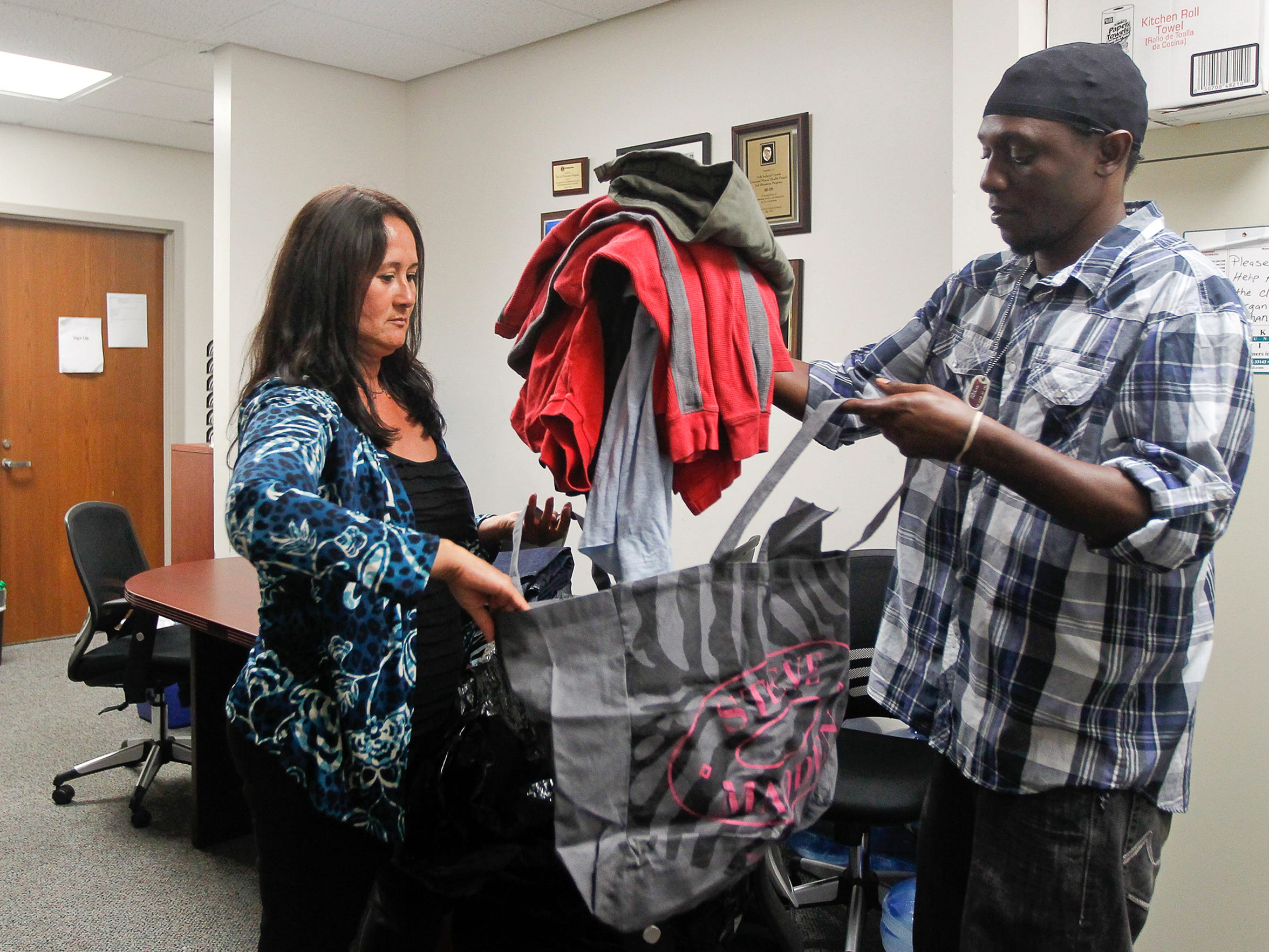 Julie Reed, a client specialist in the Miami-Dade County Jail Diversion Program, helps Max Joseph, a client in the program, choose donated clothes.