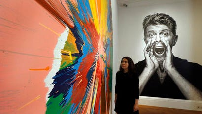 FILE - This is a Wednesday, July 20, 2016 file photo of a  woman as she looks at a painting by Damien Hirst in front of a portrait of David Bowie at Sotheby's in London. Buyers have snapped up modern artworks collected by David Bowie at a London auction, with a painting by Jean-Michel Basquiat selling for more than 7 million pounds ($8.8 million). The first part of Sotheby's two-part Bowie sale netted 24.3 million pounds ($30.3 million), more than double its pre-sale estimate.