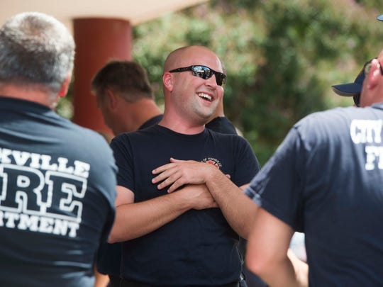 Firefighter Chris Stallings laughs with friends after eating lunch at the downtown Knoxville fire station Saturday, July 29, 2017. Knoxville man Larsen Jay threw the lunch to thank local emergency workers for responding to a life threatening accident he had 10 years ago.