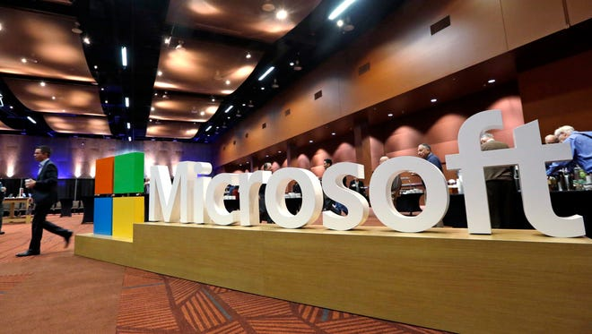 A man walks past a Microsoft sign at the annual Microsoft shareholders meeting  in Bellevue, Wash on Nov. 30, 2016.On July 7, 2017, Microsoft announced plans to shed thousands of jobs in a major reboot to focus on its fast-growing cloud-computing business.