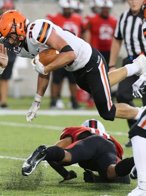 Drew Robinson (29) of Hoover leaps over Brian Pinkney (10) of McKinley during their game at Tom Benson Hall of Fame Stadium on Friday, Sept. 4, 2020. Robinson scored a touchdown a few plays later.