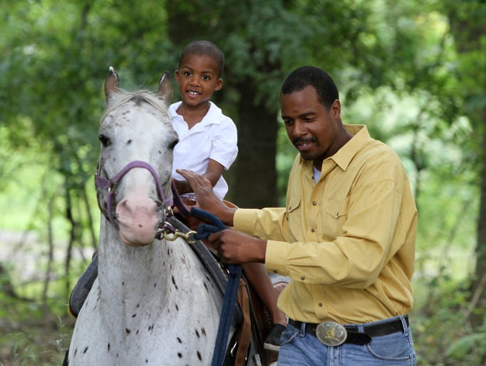 "Five-year-old Sherman Glasco takes a ride on a horse with help from Bruce Alston of Jersey Horsemen during the ""Sunday Funday"" event at Travelers Fellowship Community Church, Sunday, August 24, 2014, in Piscataway, NJ. Photo by Jason Towlen"