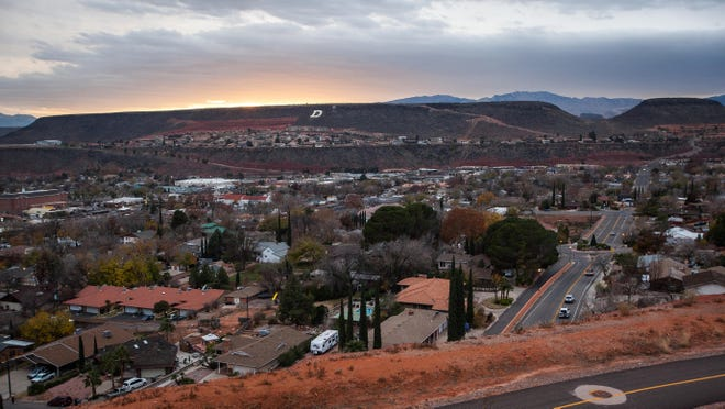 Dark clouds gather as the sun sets over St. George on Tuesday, December 3, 2013.
