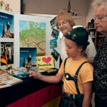 """Friends of the German Language members Christine Conway, left, Tiegan Jordan, 10, and Ingrid Luchini gather as Tiegan reads a German book titled """"Die Olchis fliegen in die Schule"""" which translates to """"The Olchis Fly to School."""""""