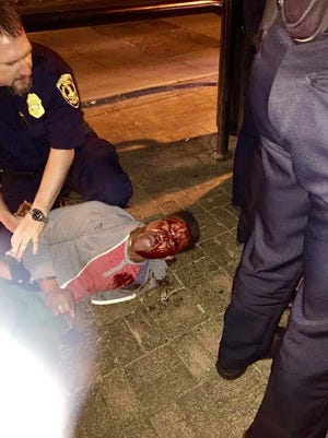 In this photo provided by Bryan Beaubrun, Martese Johnson is held down by an officer Wednesday, March 18, 2015, in Charlottesville, Va. Gov. Terry McAuliffe is calling for an investigation.