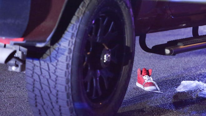 A sneaker rests on the road after a child was struck and trapped under a pickup truck on the 1200 block of Linden Street about 5:45 pm Tuesday.