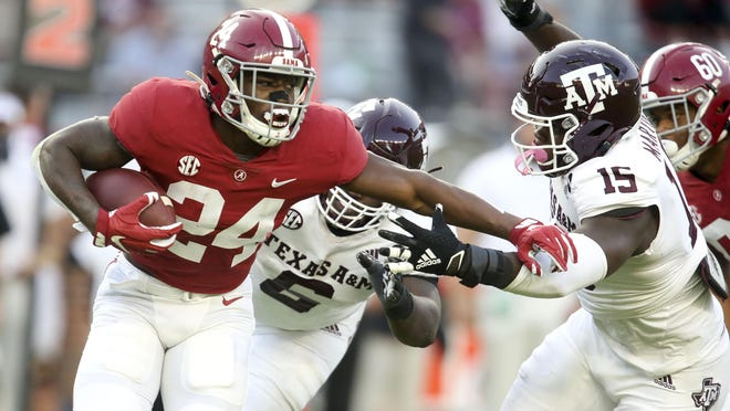 Alabama running back Trey Sanders tries to get away from Texas A&M defensive lineman Jeremiah Martin during the Crimson Tide's 52-24 win Saturday at Bryant-Denny Stadium.