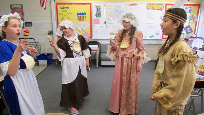 Van Zant Elementary School fifth-graders Grace Danielewicz (far left), Sophia Stancati, Michaela Belskis, and Shinbi Bae learned to play traditional colonial games, such as getting a ball in a cup, on Colonial Day at the school on March 24.