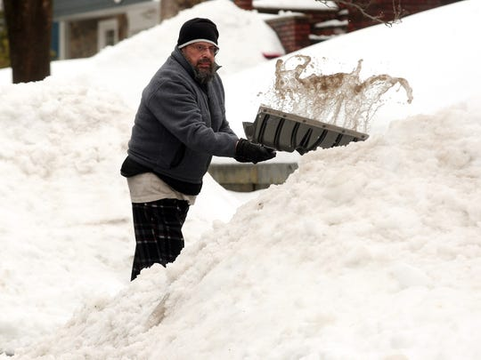 Joseph Dubov of Morristown shovels slush from his driveway in preparation for yet another storm to hit the Northeast bringing 4 more inches of snow to Morris County. Today's snow is likely to be particularly heavy with rain and sleet contributing to the weight.