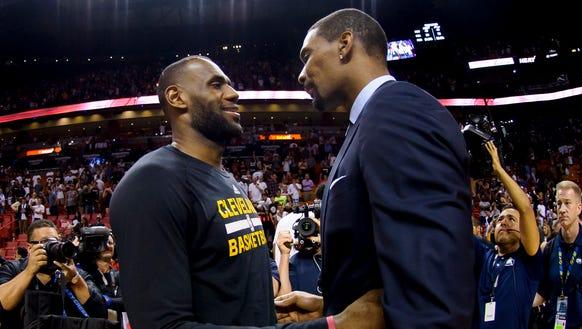 Cleveland Cavaliers forward LeBron James (left) talks