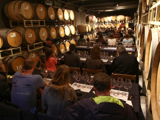 Ryan Clifford leads a group of visitors through a futures tasting in the barrel room at WIllamette Valley Vineyards on Friday, Nov. 27, 2015.